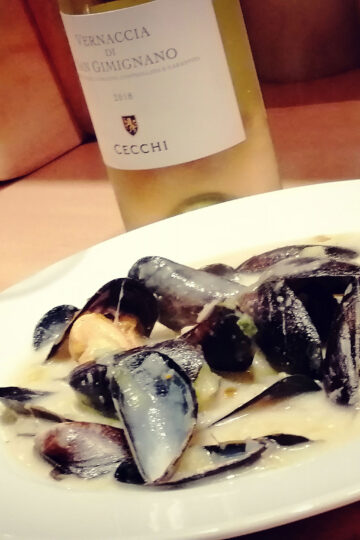 Teller mit Muscheln und Weinglas